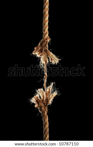 Taut rope breaking apart isolated over a black background