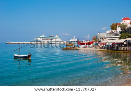 Taverns with red boat in the port of the Greek island against a cruise ship. Mykonos.