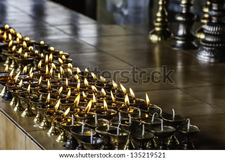 Tawang, Arunachal Pradesh, India. Buttermilk candles burn as a votive offering by monks for the Dalai Lama at the ancient 17th Century Buddhist monastery at Tawang, Arunachal Pradesh, India.