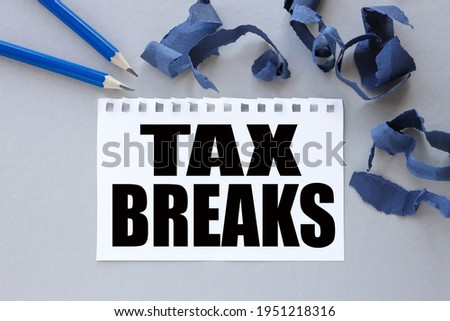 TAX BREAKS. text on white notepad paper. near torn blue paper Stock photo ©