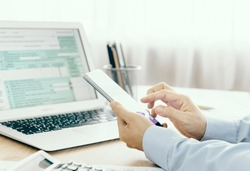 Tax concept, accountants are filling online tax information using smart phones.