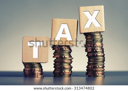 Tax Concept with wooden block on stacked coins