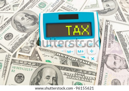 Tax concept, word on calculator with hundreds of American notes