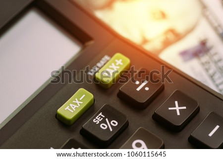 Tax cuts or reduce concept, selective focus on TAX minus buttons on calculator with background of blurred US Dollar banknotes, United States government tax overhaul policy.