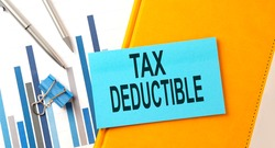 TAX DEDUCTIBLE text on sticker on yellow notebook with chart and pen
