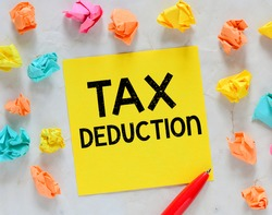 TAX Deduction words written on a small yellow piece of paper.