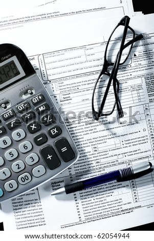 Tax form, a calculator, a pen on the table