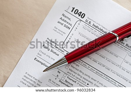 Tax form and a red pen - stock photo