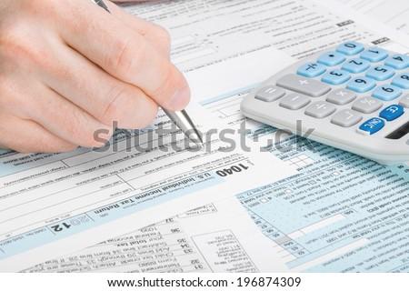 Tax Form 1040 - man filling out tax form