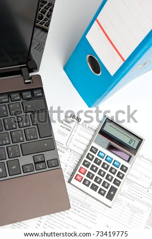 Tax form, part of laptop, calculator, office folder and pen