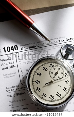 Tax form, red pen and stopwatch