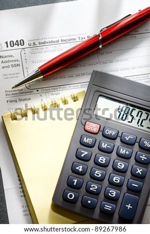Tax form, red pen, notepad and calculator