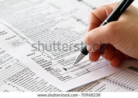 tax form with hand and pen