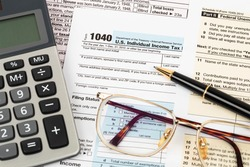 Tax form with pen, calculator, and glasses taxation concept
