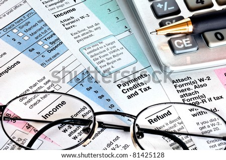 Tax forms with calculator, glasses and pen.