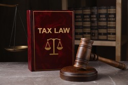 Tax law book and gavel on grey marble table