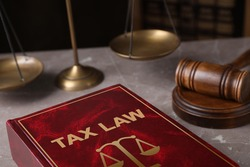 Tax law book and gavel on grey marble table, closeup