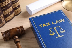 Tax law book and gavel on wooden table