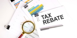 TAX REBATE text on white paper on light background with charts paper