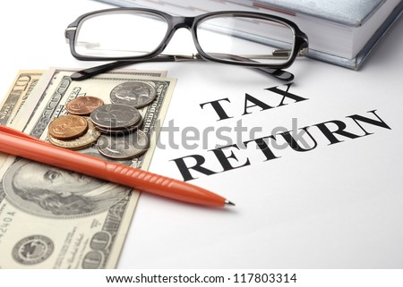 Tax return papers with glasses, pen and money