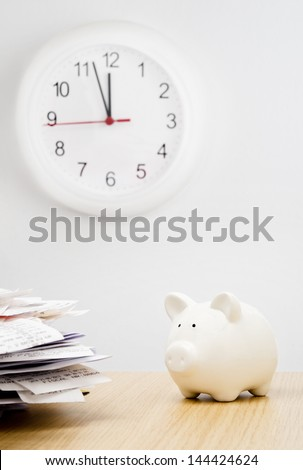 Tax time. A stack of bills next to a piggy bank with a clock behind