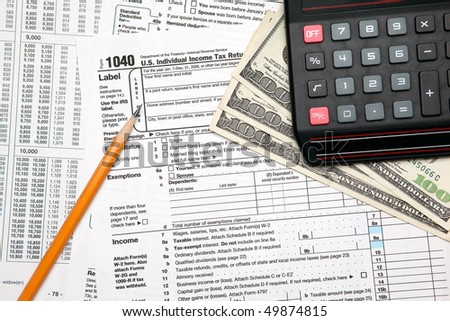 Tax time - Closeup of U.S. 1040 tax return with pencil and calculator
