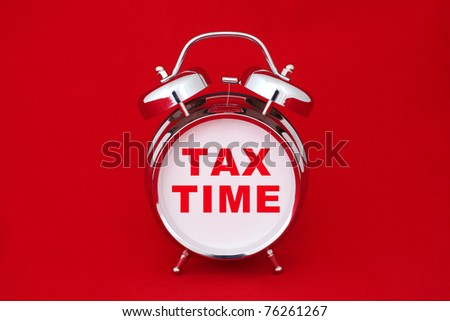 tax time on the alarm clock face. isolated on red