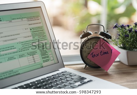 tax time post-it on alarm clock and Individual income tax return form online.