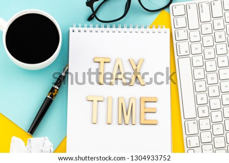 Tax Time - wooden letters with tax form, and cup of coffee. #1304933752