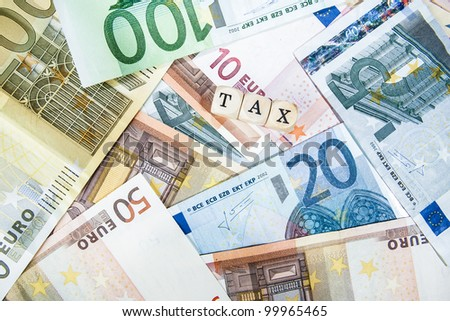 Tax written with cubes / letters and different euro bills as a background