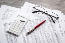Taxes calculation concept. Financial documents, calculator, glasses on grey background