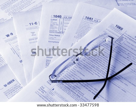Taxes forms and glasses. Toned blue. Shallow DOF.
