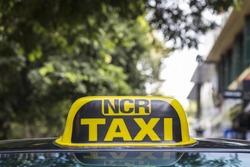 taxi cab sign of taxi in Delhi with city background, India. NCR is short name, full name is National Capital Region. It's mean area around Delhi such as Gurgaon