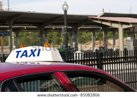 Taxi car waits for a pickup at the train stop.