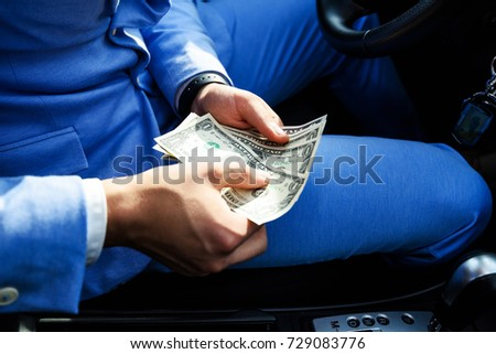 Taxi driver gives change to a client. The payment in the taxi concept. Man calculates money in the car.