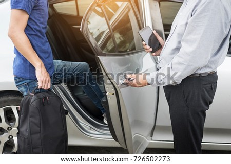 Taxi driver greeting his passengers with their luggage on the sidewalk of a modern city