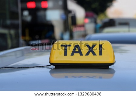 Taxi light sign or cab sign in yellow color with black text on the car roof at the street blurred background, Myanmar.
