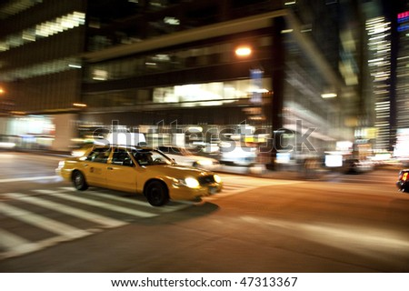 Taxi on an urban street at night, blurred as it races down the street.