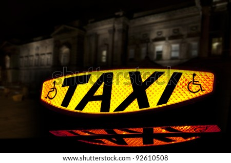 Taxi sign lit up showing the word Taxi and the disabled symbol with a reflection