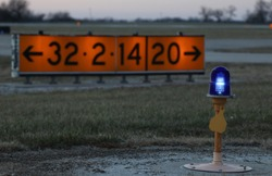Taxiway light in front of airfield runway signage