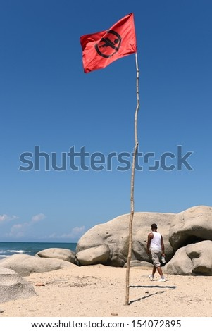 TAYRONA, COLOMBIA - NOVEMBER 13:  Tayrona National Park - a huge protected area of 12 000 hectares, on the Caribbean coast of Colombia. Red flag on the beach in November 13, 2012 in Colombia.
