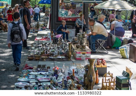 Tbilisi, Georgia -  June 18, 2018: A tourist taking picture of traders on Dry Bridge Flea market in Tbilisi selling Soviet badges, bijou, retro junk stuff, tableware sets, dishes, carpets #1133980322