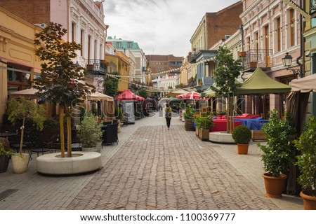 Tbilisi, Georgia - May 26 2018: Agmashenebeli avenue walking street with cafes, restaurants, bars, tourists, shops, souvenirs, wine shops. Cozy little streets promenade in Tbilisi old city center. #1100369777