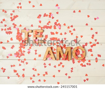 Te Amo meaning I Love You in Spanish written with the block letters covered with red heart shaped confetti over the wooden background Stockfoto ©