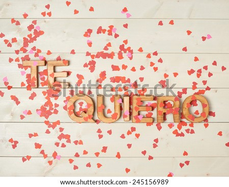 Te Quiero meaning I Love You in Spanish written with the block letters covered with red heart shaped confetti over the wooden background Stockfoto ©