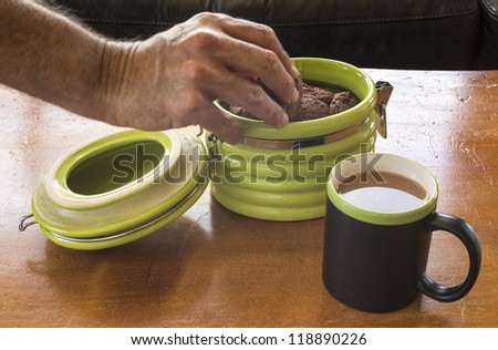Tea and Cookies/ chocolate fudge cookies in a green, retro cookie jar with a mug of hot tea #118890226