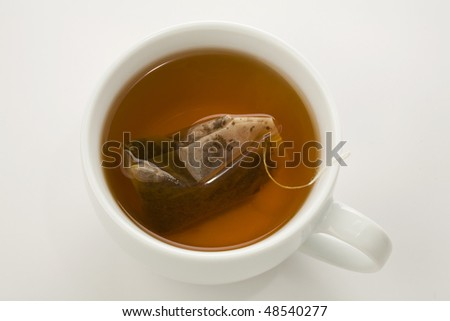 tea bag brewing in a white cup isolated on white