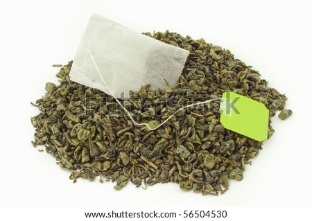 Tea bag inside a mount of dried green tea leaves