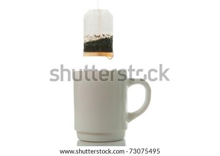 Tea bag over mug on a white background