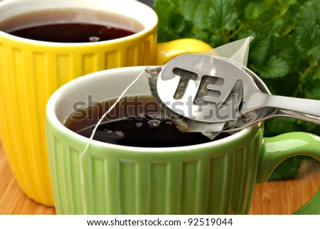 Tea bag squeezer with tea bag and colorful mugs filled with freshly brewed hot tea.  Lemon balm herb plant in soft focus in background.  Macro with shallow dof.  Selective focus on the word - TEA.